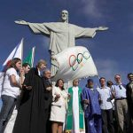 Religious leaders pray next to Olympic Flag by Christ the Redeemer, Rio de Janeiro